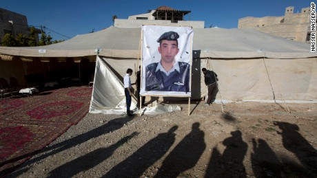 A banner with a picture of Jordanian pilot, Lt. Muath al-Kaseasbeh, who is held by Islamic State group militants, is being raised by workers near a tent prepared for receiving supporters, in Amman, Jordan, Friday, Jan. 30, 2015. (AP Photo/Nasser Nasser)