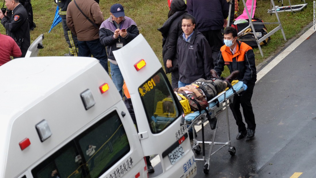 Rescue personnel put an injured passenger into an ambulance on February 4.