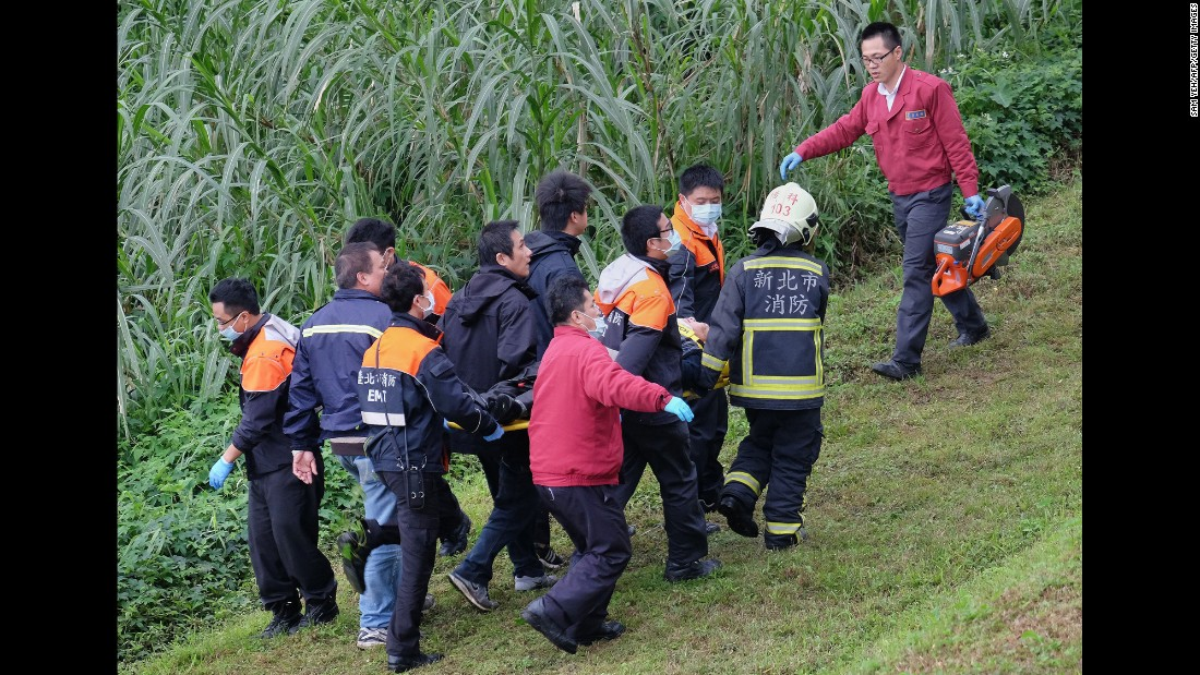 Rescuers carry an injured passenger on a stretcher up the riverbank on February 4.