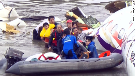 Rescue personnel work to free passengers from a TransAsia ATR 72-600 turboprop plane that crash-landed into a river outside Taiwan's capital Taipei in New Taipei City on February 4, 2015.