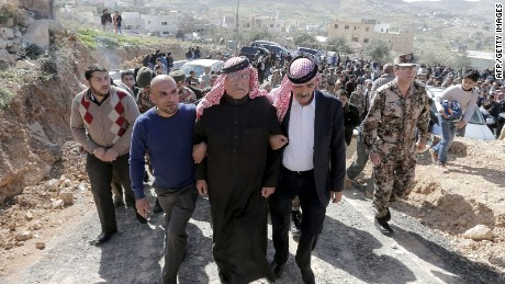 Safi (C), the father of Jordanian pilot Maaz al-Kassasbeh, who was killed by Islamic State (IS) group militants on February 3, 2015 after he was captured by IS when his plane went down in Syria in December, is surrounded by family members and security forces during a mourning ceremony at the headquarters of the family's clan in the Jordanian city of Karak on February 4, 2015. Jordan executed two death-row Iraqi jihadists, including a woman, on February 4 after vowing to avenge the burning alive of its fighter pilot Maaz al-Kassasbeh. Jordan had promised to begin executing Islamic extremists on death row in response to the murder of the pilot. AFP PHOTO / KHALIL MAZRAAWIKHALIL MAZRAAWI/AFP/Getty Images
