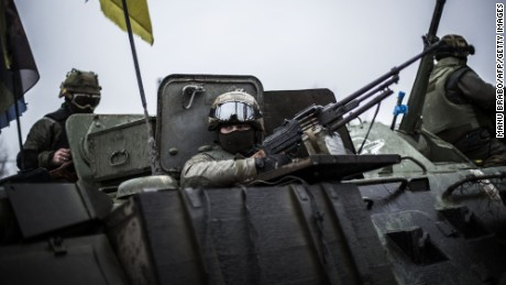Ukrainian soldiers are seen in an armoured vehicle topped with a Ukrainian flag near the city of Artemivsk, in the Donetsk region, before heading to the city of Debaltseve about 45 km away, on February 1, 2015. Civilians fleeing the besieged east Ukrainian town of Debaltseve came under withering artillery fire from pro-Russian separatists on February 1, with security forces vowing to fight to the end to defend the key transport hub. AFP PHOTO / MANU BRABO        (Photo credit should read MANU BRABO/AFP/Getty Images)