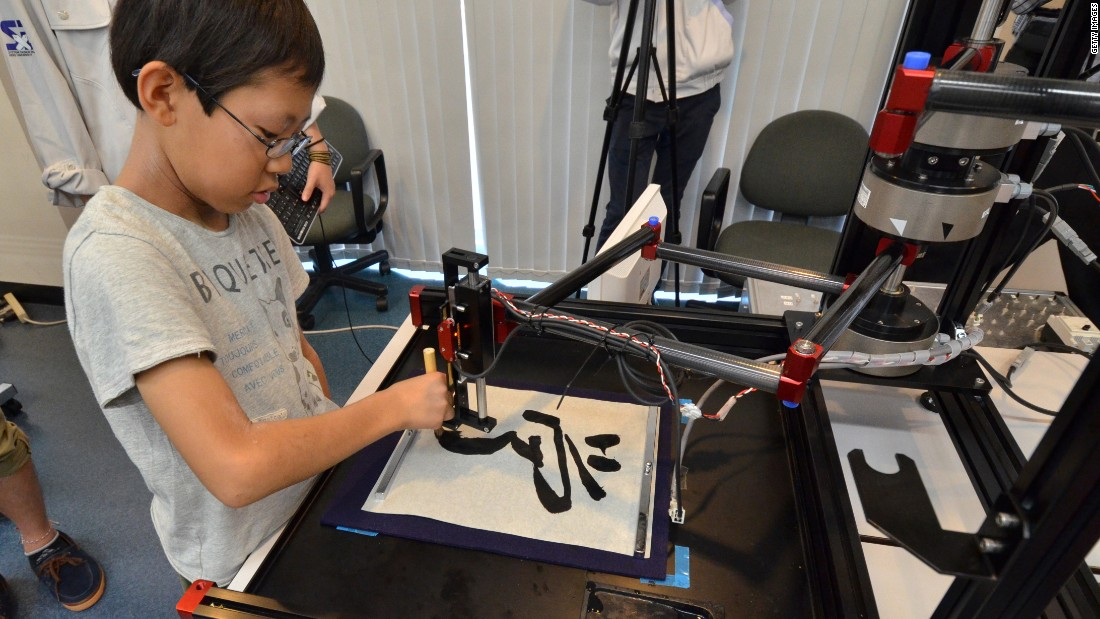 A boy writes a Chinese letter for 'study' with a calligraphy robot, which mimics the exact brush strokes of a master calligrapher, at a science workshop for elemenatry children at Keio University in Yokohama, suburban Tokyo on July 30, 2013. The motion copy robot, developed by Japan's Keio University associate professor Seiichiro Katsura, can recreate master works and the users can experience the same pressure and the same gestures of brush works by master painters or calligraphers.