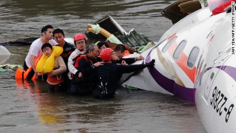 Rescue personnel (in helmets) help passengers as they wait to be transported to land from the wreckage of a TransAsia ATR 72-600 turboprop plane that crash-landed into the Keelung river outside Taiwan's capital Taipei in New Taipei City on February 4, 2015. At least 16 people were killed when TransAsia Aiways Flight GE235 with 58 people on board clipped a road bridge and plunged into the river in Taiwan, in the airline's second crash in just seven months. AFP PHOTO / SAM YEH (Photo credit should read SAM YEH/AFP/Getty Images)