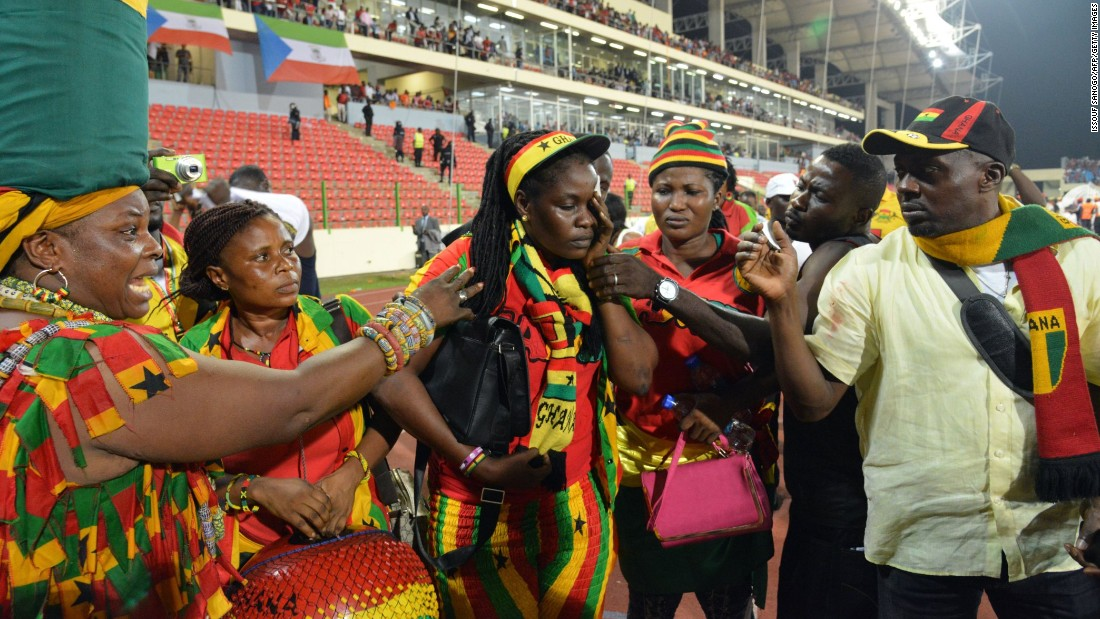 A Ghanaian fan holds her face while standing beside the pitch after the match, which was played in Malabo, Equatorial Guinea.