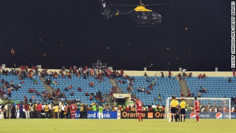 A police helicopter flies over the stadium during an interruption of the 2015 African Cup of Nations semi-final football match between Equatorial Guinea and Ghana in Malabo, on February 5, 2015. Play was halted eight minutes from time in the Africa Cup of Nations semi-final between hosts Equatorial Guinea and Ghana when missiles were thrown on the pitch.