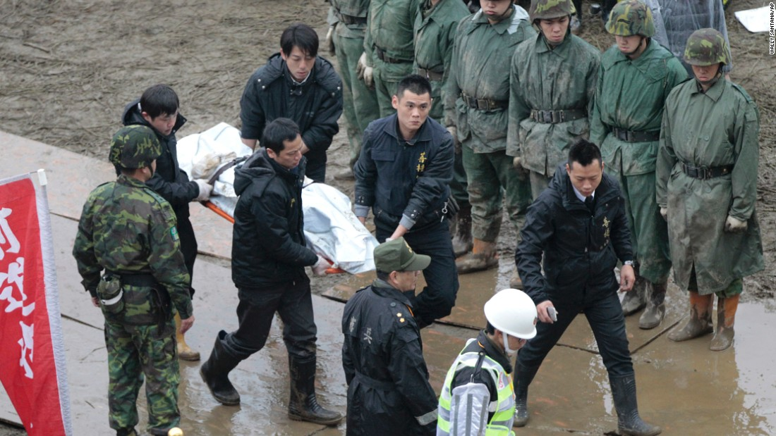 Emergency personnel carry a body recovered from the water on February 6.