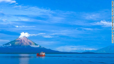 A boat tour makes its way through Lake Nicaragua with Ometepe Volcano as the background.