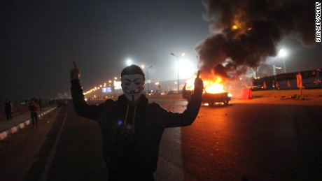 A masked man gestures near a burning car outside a sports stadium in Cairo's northeast district during clashes between supporters of Zamalek FC and security forces.