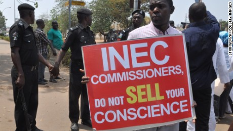 People hold signs to protest postponement of elections, as police officers hold hands to blocks protesters, on February 7, 2015 in Abuja. The six-week delay was announced on February 7, 2015 after security chiefs said the military needed more time to secure areas under the control of Boko Haram, the Islamist extremists who have seized swathes of northeastern Nigeria. Presidential and parliamentary elections will now be held on March 28 instead of February 14, said Attahiru Jega, chairman of the Independent National Electoral Commission (INEC). AFP PHOTO / STRINGER (Photo credit should read STRINGER/AFP/Getty Images)