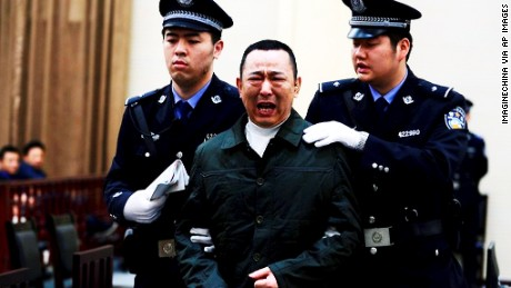 Liu Han, center, cries as he is escorted by police officers during his trial on 16 April 2014.