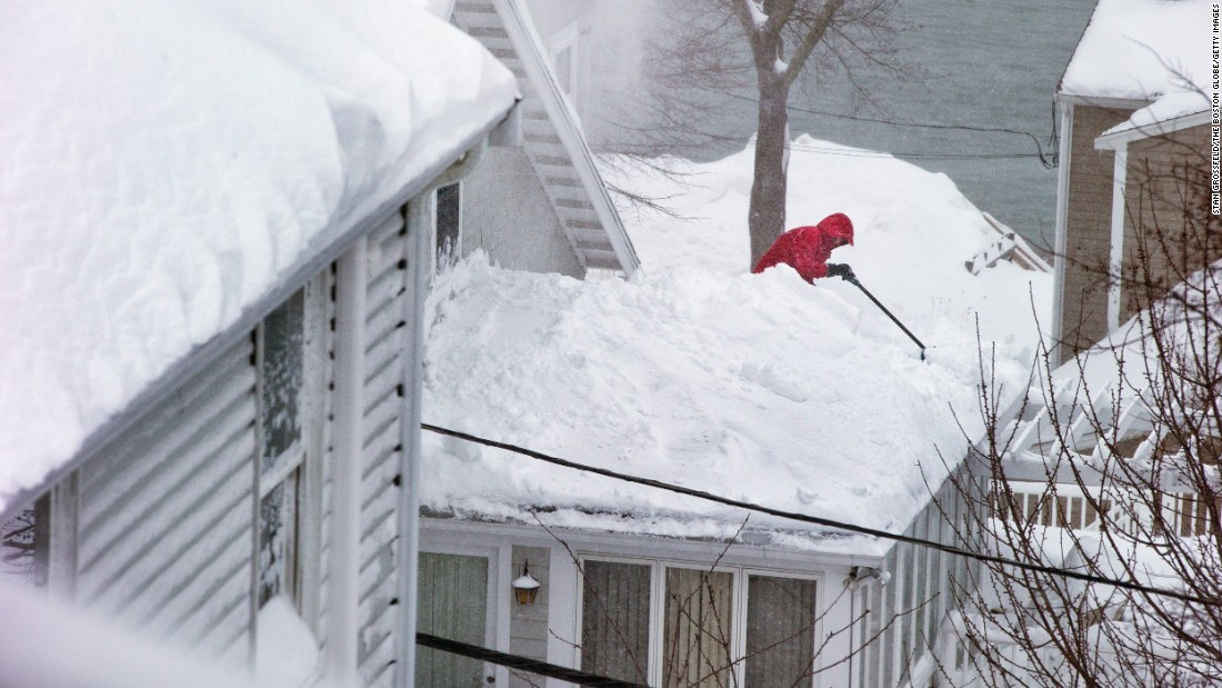A man climbs onto his roof to clear piles of snow in Quincy, Massachusetts, on February 9.