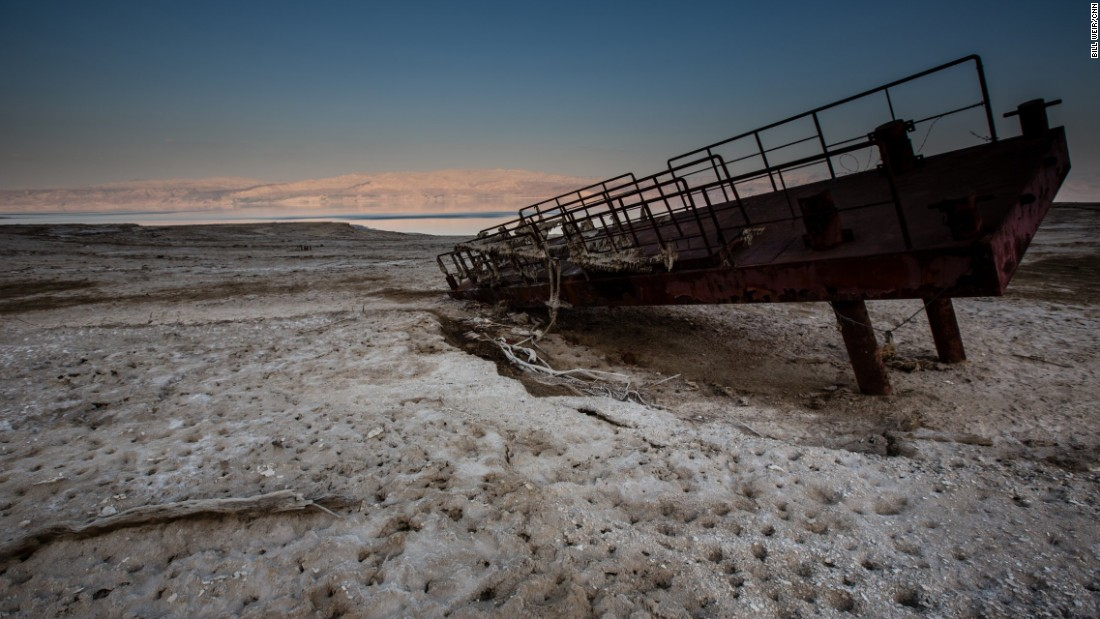 A rusty old dock lies atop a desert encrusted in salt. What used to be the shoreline of the Dead Sea now lies hundreds of feet from the water's edge.