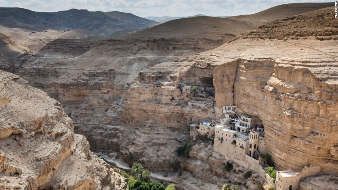 "St. George's Monastery, carved into the side of a cliff near Jericho, stands alone at the bottom of Wadi Qelt, often associated with the biblical ""valley of the shadow of death."""