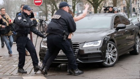 "Police detain a topless Femen activist who jumped on the car carrying former IMF chief Dominique Strauss-Kahn (not seen) upon his arrival for his trial in Lille, northern France, on February 10, 2015. Three topless women from the protest group Femen jumped on the car of Dominique Strauss-Kahn as the former IMF chief arrived to testify at his trial for ""aggravated pimping."" With slogans scrawled on their half-naked bodies and hurling insults at the car, the three protesters were quickly rounded up by police as the car entered an underground parking area. AFP PHOTO / DENIS CHARLETDENIS CHARLET/AFP/Getty Images"