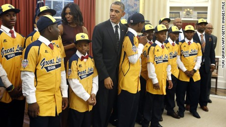 US President Barack Obama and First Lady Michelle Obama greet the 2014 US champion Jackie Robinson West All Stars Little Baseball League in the Oval Office of the White House in Washington, DC on November 6, 2014. AFP PHOTO/YURI GRIPAS        (Photo credit should read YURI GRIPAS/AFP/Getty Images)