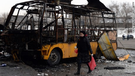 A woman walks past a destroyed bus in Donetsk on February 11, 2015.