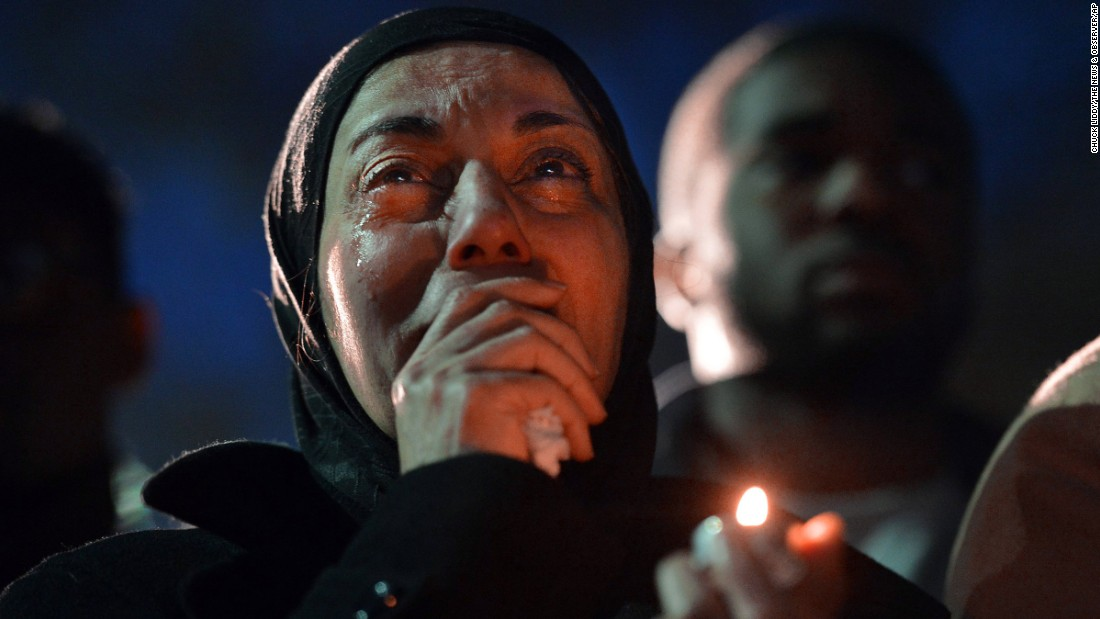 A woman cries during a vigil on Wednesday, February 11, as she watches photos projected on a screen of three people killed at an apartment near the University of North Carolina at Chapel Hill. Much of the college community is grieving at vigils and prayer services after three Muslim students -- Deah Shaddy Barakat, 23; his wife, Yusor Mohammad, 21; and her sister, Razan Mohammad Abu-Salha, 19 -- were found shot to death Tuesday, February 10. Craig Stephen Hicks has been charged with murder in their deaths.