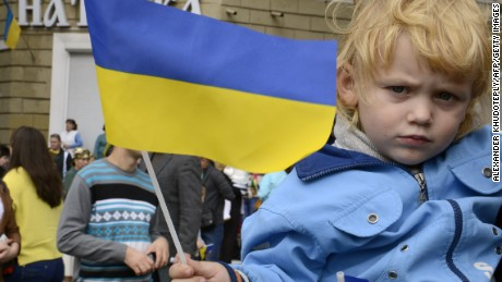 A boy holds a Ukrainian flag as Ukrainian soldiers parade in Mariupol during the celebrations marking the city day on September 20, 2014.