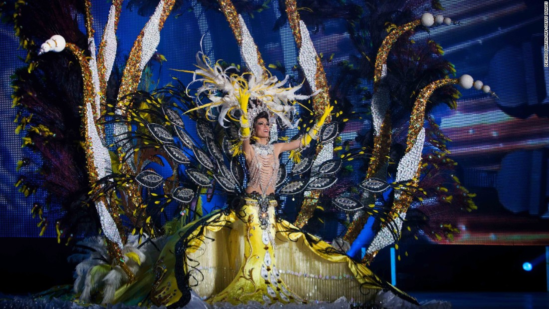 A nominee for Queen of the Carnival of Santa Cruz shows off her outfit on stage Wednesday, February 11, in Santa Cruz de Tenerife, Spain.
