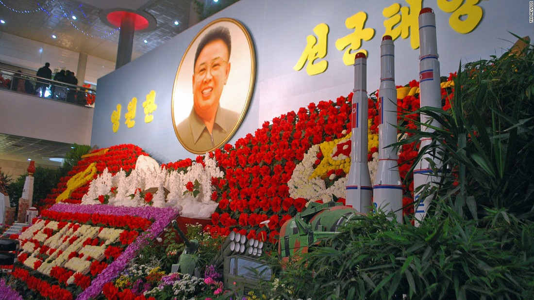Yep, those are missiles in front of a portrait of Kim Jong Il surrounded by a display of Kimjongilias, the colorful flowers named after him.