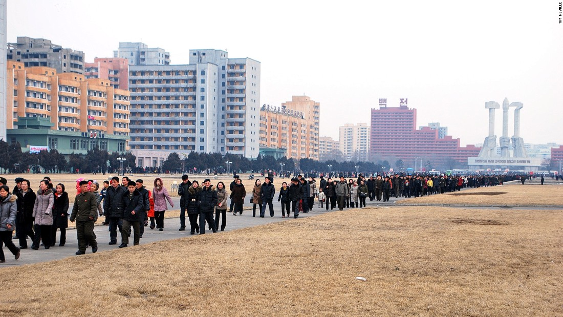Citizens walk in orderly fashion to a show celebrating Kim Jong Il. The Korean Workers Party Monument, a Pyongyang landmark, is in the distance.