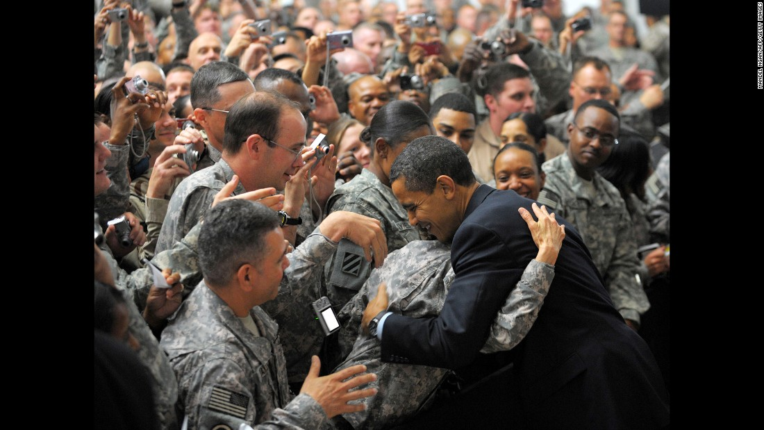 A soldier hugs Obama during his surprise visit to Camp Victory just outside Baghdad, Iraq, in April 2009.