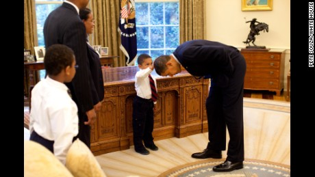 Obama bends over so the son of a White House staff member can pat his head during a visit to the Oval Office in May 2009. The boy wanted to know if Obama's hair felt like his.