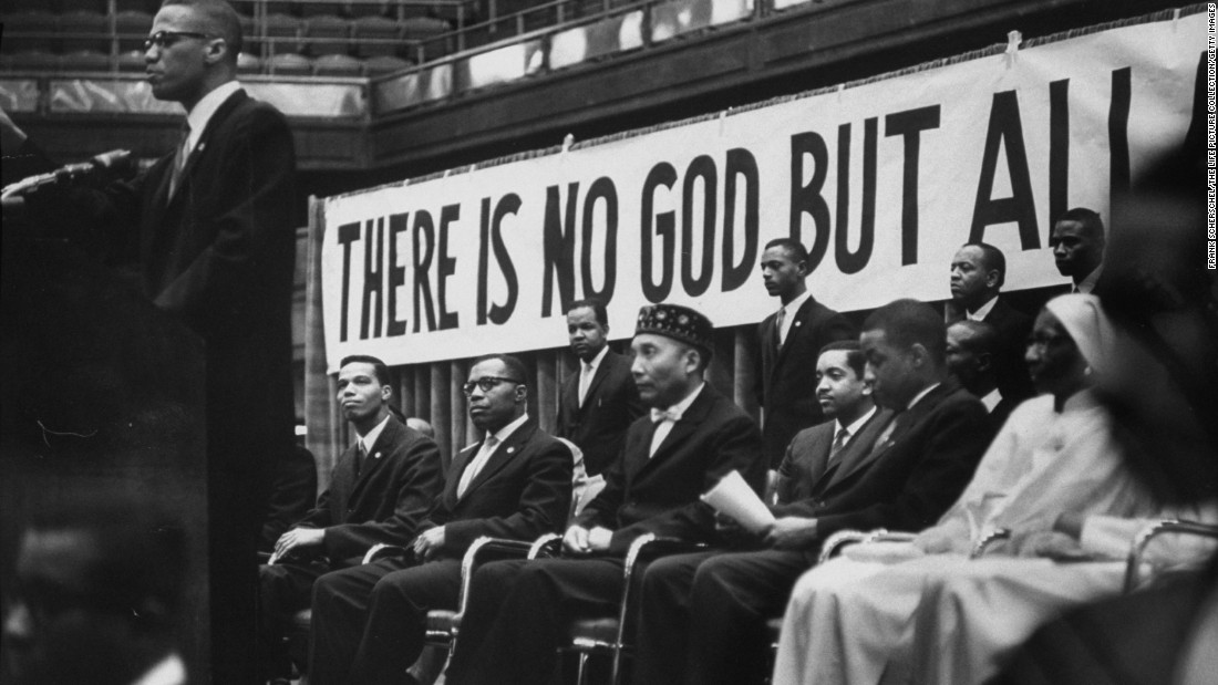 "Nation of Islam leader Elijah Muhammad, seated in the hat, listens as Malcolm X speaks at a Nation of Islam convention in Chicago in February 1961. It was Malcolm X who bestowed the title ""Honorable"" to Muhammad. <br />"
