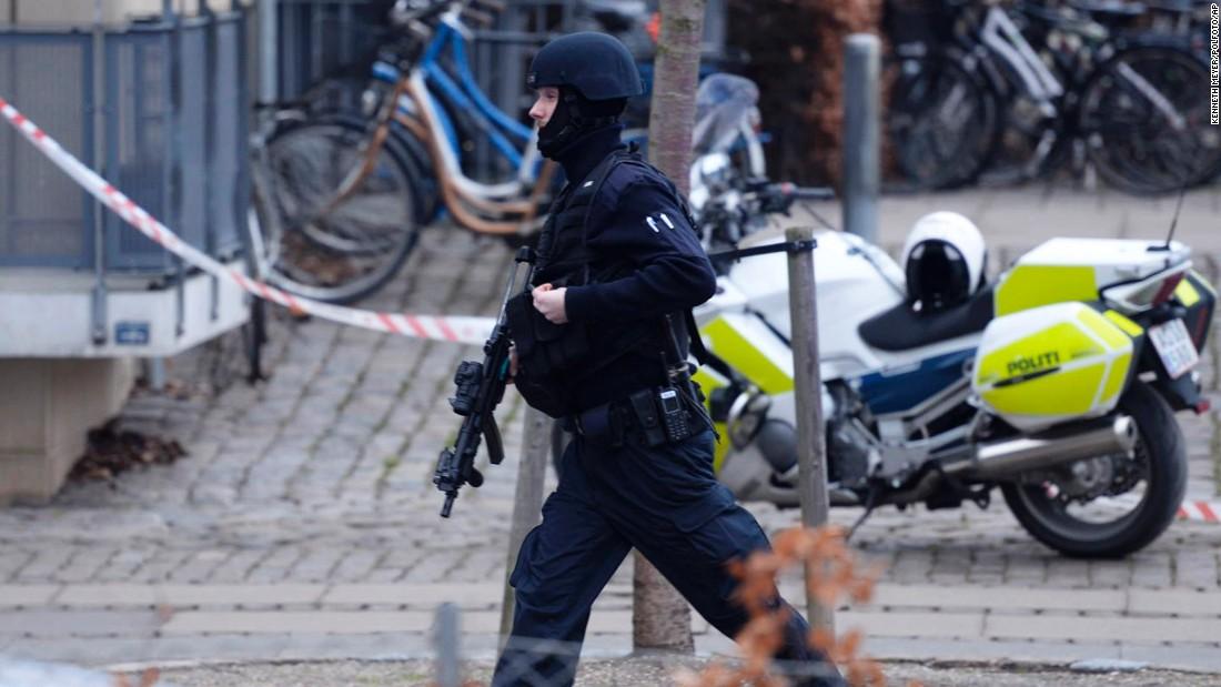 An armed security officer runs down a street near a venue.