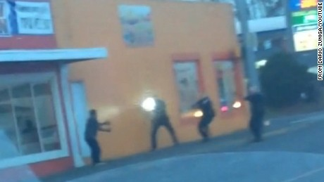 In an frame taken from a YouTube video posted by Dario Zuniga, Antonio Zambrano-Montes, 35, (far left) is seen immediately before he was fatally shot by Pasco, Washington, police officers who confronted him (three, to the right).  The officer closest to him is holding a flashlight.