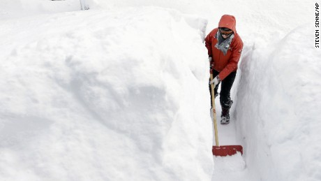 Kim Taylor, of Norwood, Massachusetts, shovels a path in the snow in front of her home on February 15.