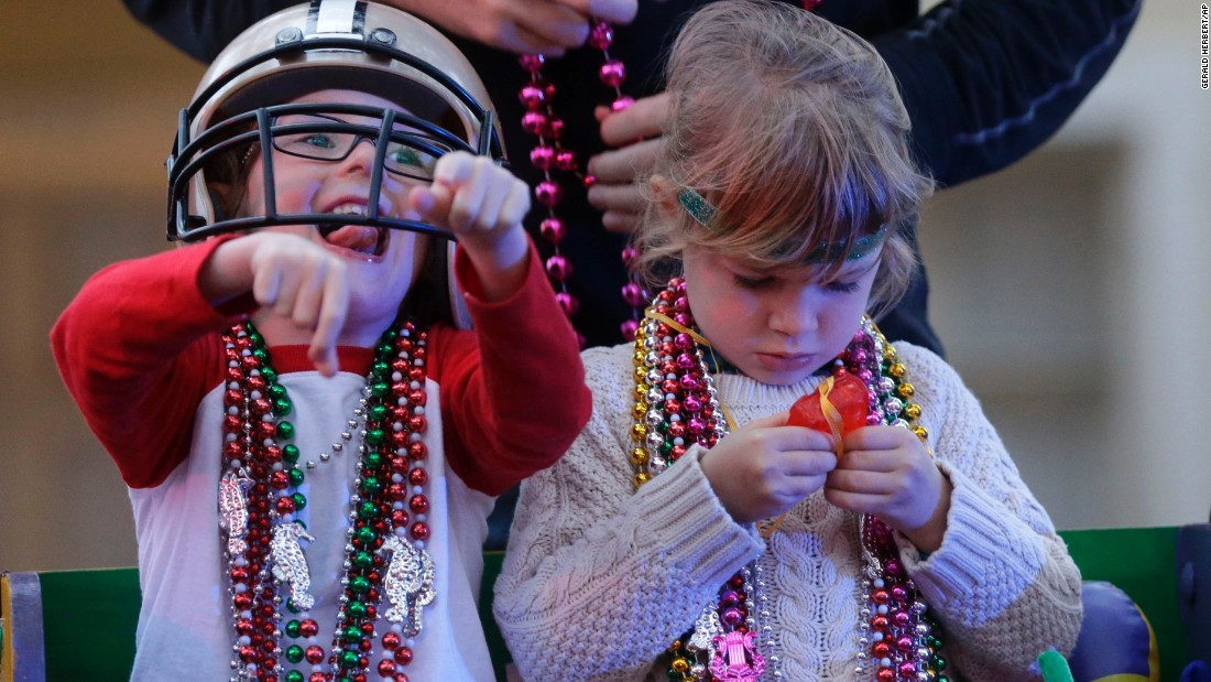 Barker Curry, 4, cheers while his cousin Sophia Curry, 3, looks at one of her trinkets during the Krewe of Proteus Mardi Gras parade on February 16.