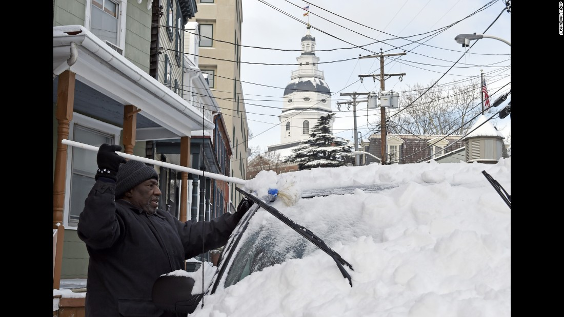 Mike Simms clears snow from his car in Annapolis, Maryland, on Tuesday, February 17. Wintry weather spread along the East Coast and across parts of the South leaving tens of thousands without power.