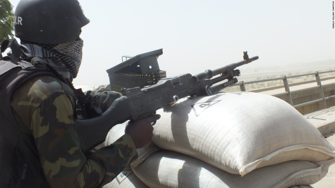 A Cameroonian soldier points his gun across the El Beid Bridge into Gambaru, Nigeria. Gambaru is considered one of the strongholds of Boko Haram.