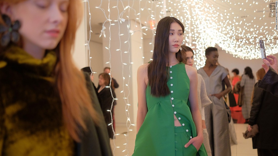 A model poses in a playful, Kelly green pantsuit for Rosie Assoulin.