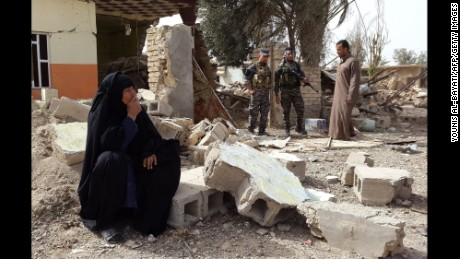 A woman looks at her destroyed home after returning to the village of Al-Mansuriya, Iraq, on Saturday, February 14.