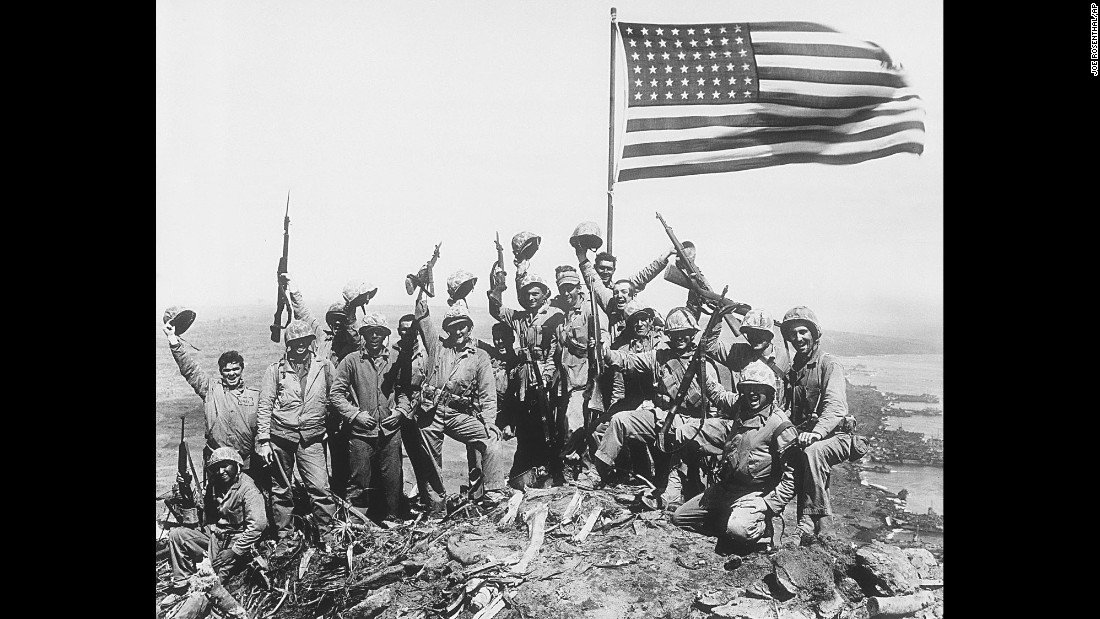 "This image is referred to as Rosenthal's ""Gung Ho"" photo, in which Marines posed with the second flag while raising their rifles and helmets in the air. When Rosenthal was asked later if the image was posed, he said it was. That created confusion over whether his photo of the actual flag-raising was posed. For years many people thought it was, but it really was not."