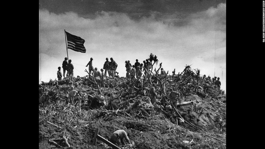 Marines gather on the summit after replacing the smaller American flag with a larger one. The photographer of this image is uncredited.