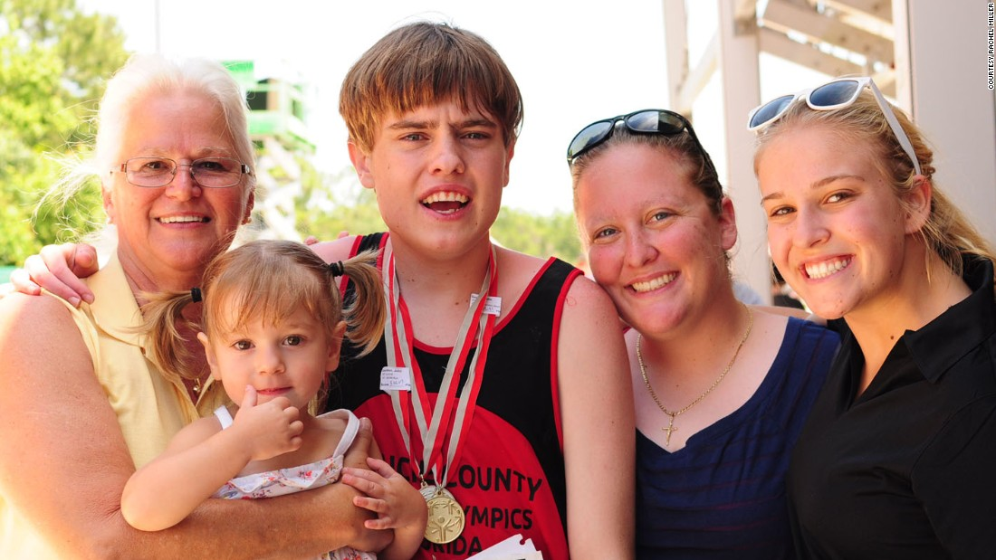 In May 2014, John won the gold medal for the 800 meters and the silver for the 110-meter hurdles at the Special Olympics State Summer Games in Orlando. Here, the 18-year-old poses with his family in a group photo. His mother, Rachel, is to his left.