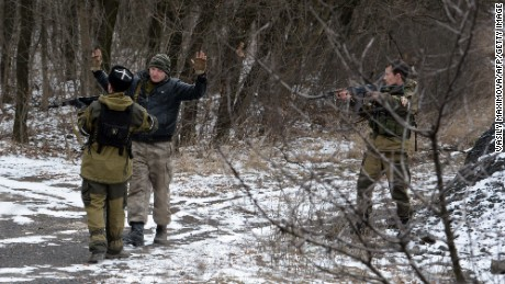 Two pro-Russian seperatists stop a man holding his arms up in the eastern Ukrainian city of Uglegorsk, 6 kms southwest of Debaltseve, on February 19, 2015.