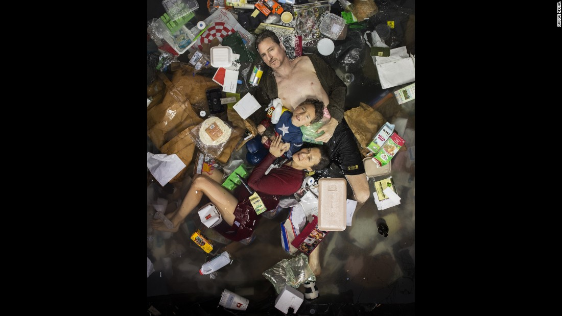 Photographer Gregg Segal gives himself a reality check by posing with one week of his family's trash.