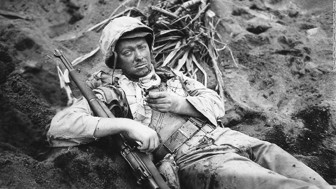 Cpl. Rudolph E. Engstrom rests in a shell hole on Iwo Jima, holding a piece of shrapnel that wounded him.