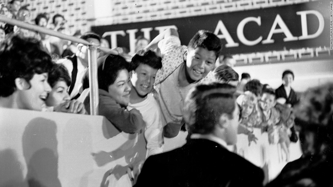 Excited fans greet Gregory Peck and his wife as they arrive at the Oscars ceremony in April 1962.