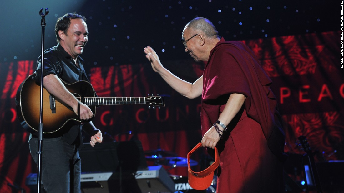 Dave Matthews greets the Dalai Lama on stage at the One World Concert at Syracuse University in New York on October 9, 2012.