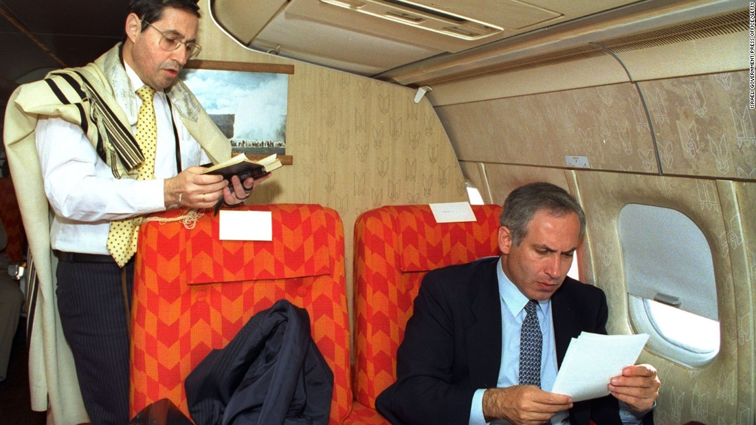 Netanyahu, as Israel's deputy foreign minister, goes through some papers as Government Secretary Elyakim Rubinstein recites morning prayers on a flight from New York to Washington in April 1989.