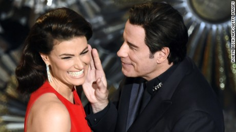 John Travolta and Idina Menzel present an award on stage together, referencing last year's flub when he mispronounced her name.