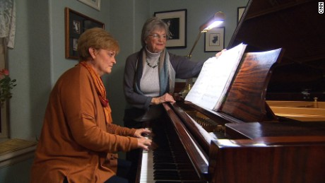 Heidi Thomas plays piano as her mother, Greta Lea Johnson, turns the pages.