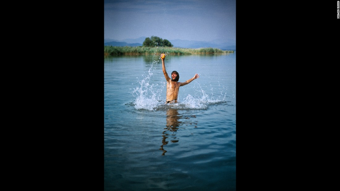 "A man splashes in the water at a 1998 gathering in Pakistan. Krivic says that Rainbow Gatherings also tend to take place in regions of the world that ""need to be healed"" after having experienced devastating conflicts."