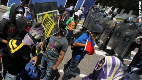 A group of students stand in front of a line of riot policemen during a protest against Venezuelan President Nicolas Maduro's government in San Cristobal, Venezuela on February 24, 2015. Venezuelan prosecutors said they would charge a policeman in connection with the death of a 14-year-old boy who was killed during the protest against the country's economic crisis. AFP PHOTO / GEORGE CASTELLANOGeorge CASTELLANOS/AFP/Getty Images
